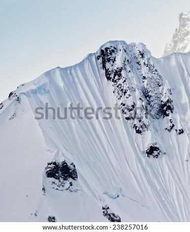 Snow capped mountain peak - stock photo