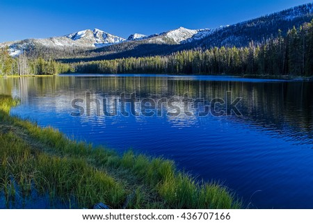 Snow-capped mountain peaks over Sylvan Pass in Yellowstone National Park reflecting in clear blue lake in late afternoon light.