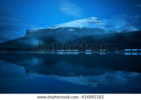 Snow capped mountain with lake reflection in a foggy dusk in Banff National Park, Canada. - stock photo