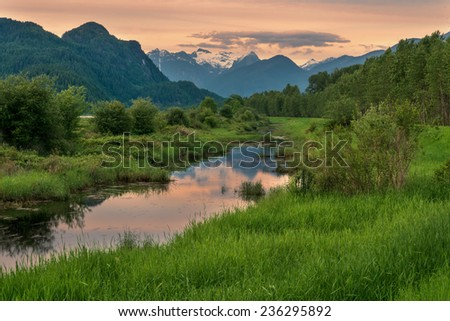 Snow capped mountains behind a still river - stock photo