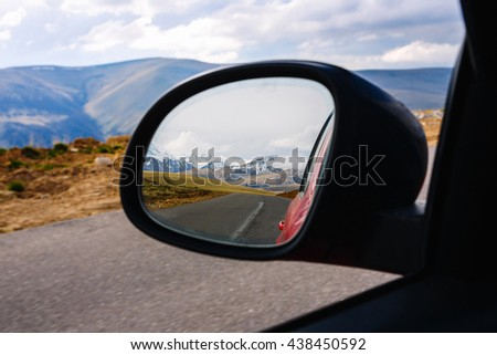 Snow-capped mountains in the reflection of the side mirror of the car. Travel - stock photo