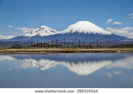 Snow capped Parinacota Volcano reflected in Lake Chungara, Chile - stock photo