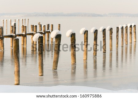 Snow Capped Pier Posts on a Frozen Lake I - stock photo