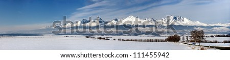 Snow capped summit of Tatry high under clear blue panoramic skies. - stock photo