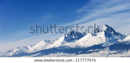 Snow capped summit of Tatry high under clear blue panoramic skies.