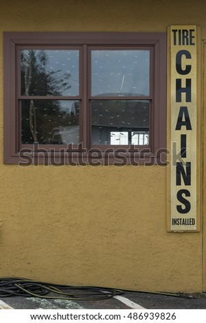 Snow chains sign on the side of a garage with a window