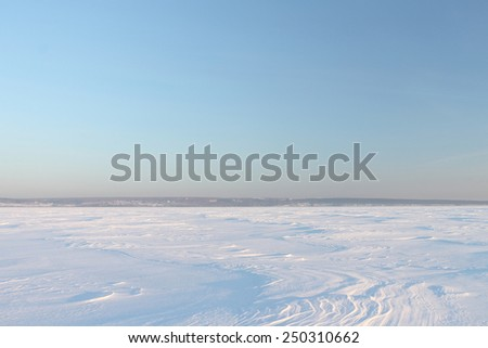 Snow cover on the frozen river in the winter at sunset