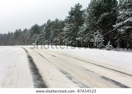 Snow-covered after a snowfall road about road turn (signs on abrupt turn are visible) - stock photo