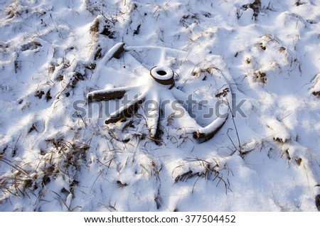Snow covered antique wooden horse carriage wheel in the meadow in winter on sunny day - stock photo