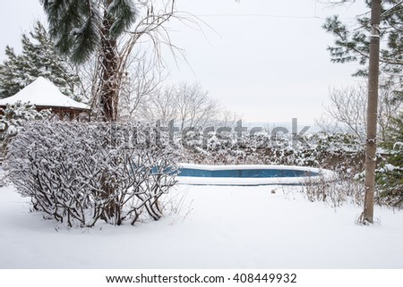 Snow covered backyard with pool. - stock photo