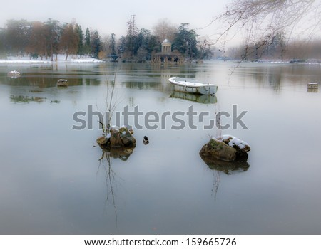Snow covered boat in the lake and Love Temple at backgrounds.  Lake Daumesnil (Vincennes forest, Paris, France). Soft focus and bleached angles.   - stock photo