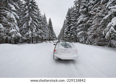 snow covered car on the winter road in forest, South Poland - stock photo