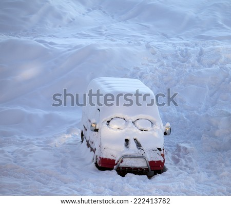 Snow-covered car with smiley in windshield. Ski resort at evening. - stock photo