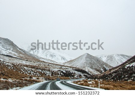 Snow covered curve road in New Zealand - stock photo