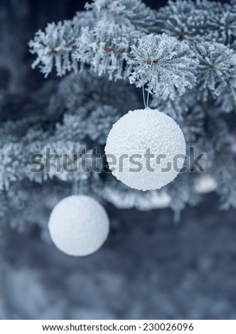 snow-covered fir tree with toy ball. - stock photo