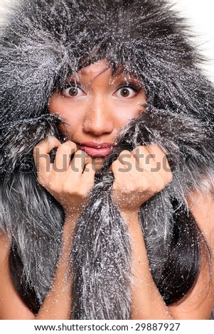 Snow-covered fur of a sable fur coat covering a head of the beautiful girl