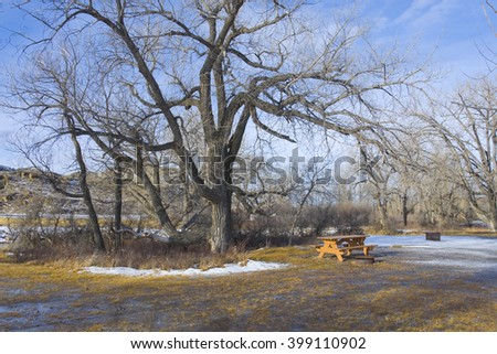 Snow Covered Ground and Picnic Table in Camp Ground - stock photo