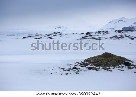 Snow covered lava fields with glacier in background, Vatnajokull national park, Southern Iceland - stock photo