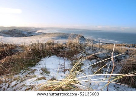 snow covered links golf course in ireland in winter with sea background - stock photo