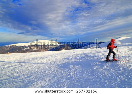 Snow covered mountain and ski touring woman ascending early in the morning