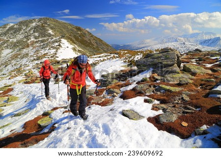 Snow covered mountain and team of mountaineers ascending a sunny ridge - stock photo