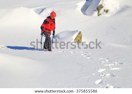 Snow covered mountain and woman carrying ice axes - stock photo