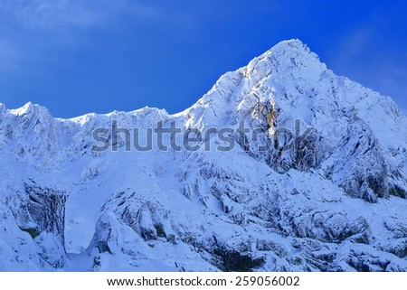 Snow covered mountain peak in sunny winter day - stock photo