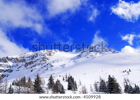 Snow covered mountain tops in Canadian Rockies with bright blue sky and snowflakes - stock photo