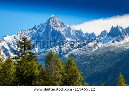 Snow covered mountains and rocky peaks in the French Alps - stock photo
