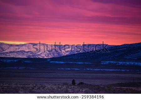 Snow-covered mountains reflect the brilliant glow of an Arizona Sunset in Houserock Valley nearby Grand Canyon National Park, Arizona. - stock photo