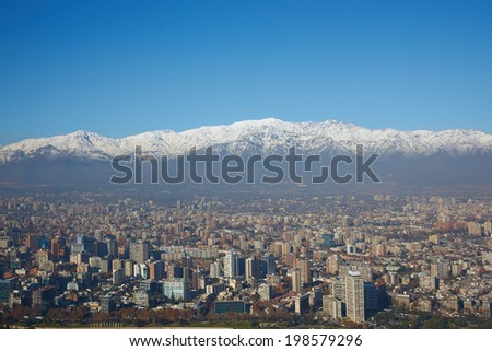 Snow covered mountains surrounding the modern high rise buildings of Santiago, the capital of Chile. View from Cerro San Cristobal. - stock photo