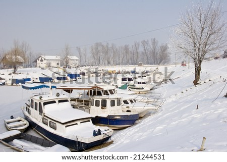 snow covered old boats in frozen marina - stock photo