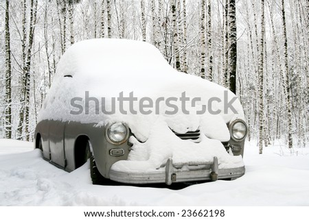 Snow covered old car in a forest