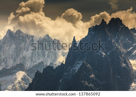 Snow covered peaks and rocky cliffs in the Alps in summer - stock photo