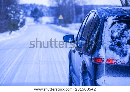 Snow-covered road in winter, car on a dangerous stretch of road covered with snow and ice.  - stock photo