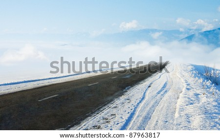 Snow covered road in winter with mountains in the distance. Travel background with mountains and auto track. Snowy highway with cloudy landscape. - stock photo
