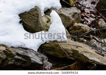 snow covered rocks in the stream - stock photo