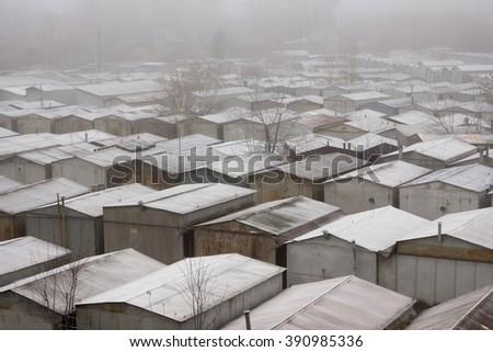 Snow-covered roofs of garages foggy day