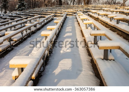 snow-covered rows of benches in a park