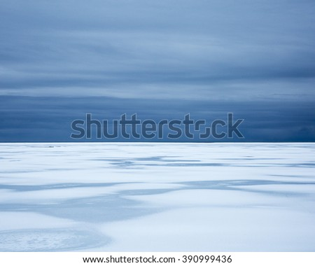 Snow covered sandar, starting to melt, under dramatic skies, Southern Iceland - stock photo