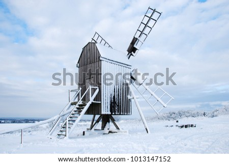 Snow covered traditional windmill at the swedish island Oland - the island of sun and wind