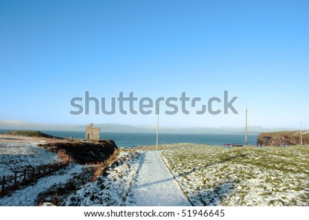snow covered view of atlantic ocean and castle in ballybunion on a frosty winters day - stock photo