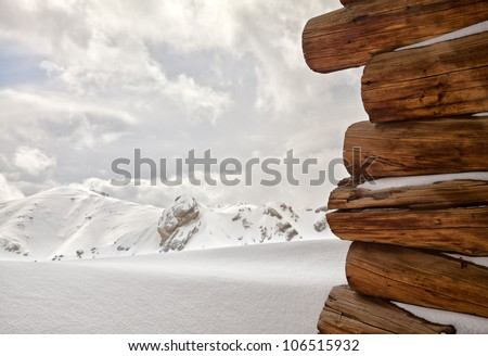 Snow covered wooden cabin facing the snowy peaks of mountains in the cold winter. - stock photo