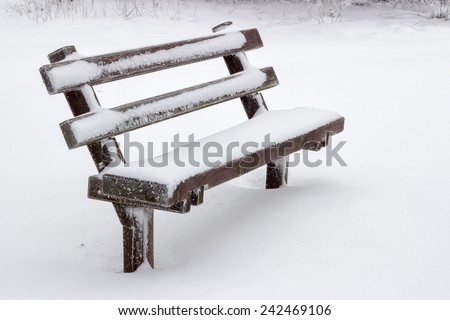 snow covered wooden sitting bench in park at winter - stock photo