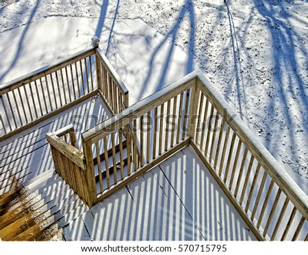 Snow covered wooden steps to a deck on a house.