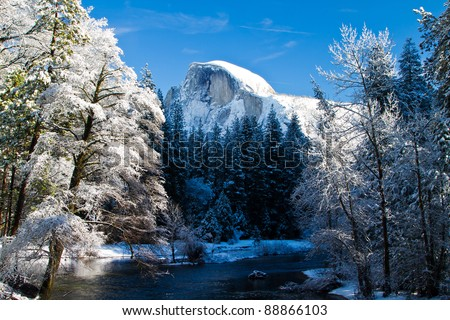 snow covered yosemite half dome and trees - stock photo
