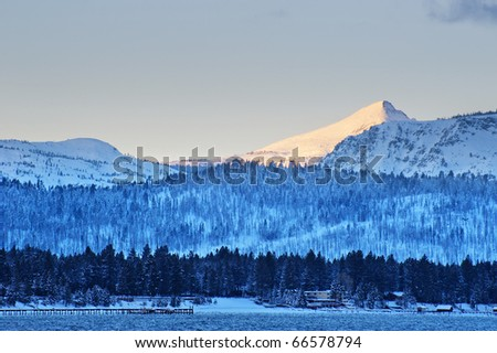 Snow covering mountain with tree in the foreground in winter time at Lake Tahoe, California - stock photo