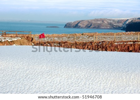 snow covering on a golf course in ireland in winter with sea and cliffs in background - stock photo