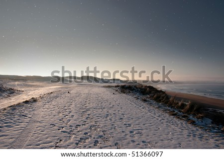snow covering on a golf course in ireland in winter with starry night sky - stock photo