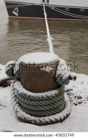 Snow covers a bollard and the rope with which a ship is lying along the quay - stock photo